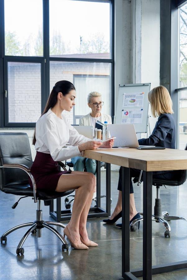 trzy fachowego bizneswomanu w formalnej odzieży pracuje przy stołem obraz royalty free