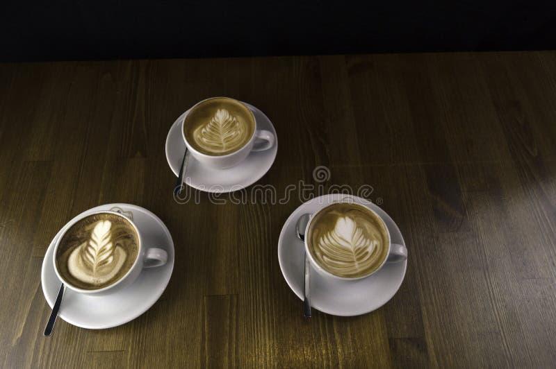 trzy filiżanki gotowej słuzyć kawę z mlekiem zdjęcia royalty free