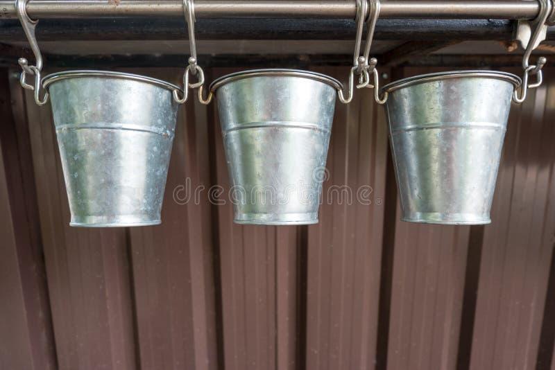 Trzy garnka nierdzewny drzewny obwieszenie od metalu poręcza fotografia stock