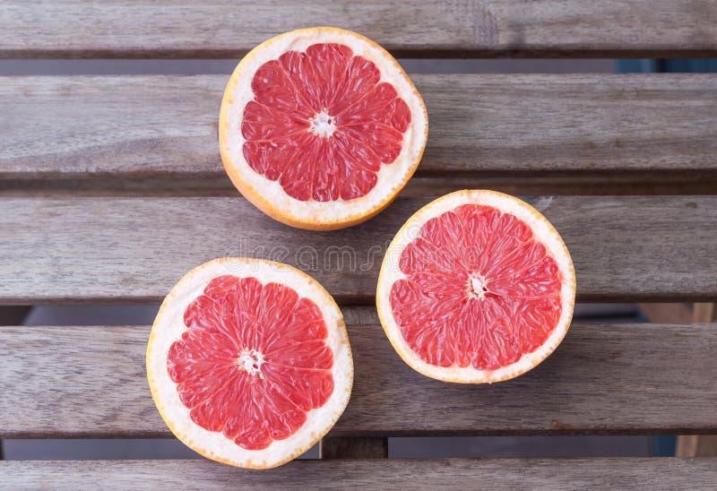 Trzy grapefruitowej połówki na drewnianym tle zdjęcie royalty free