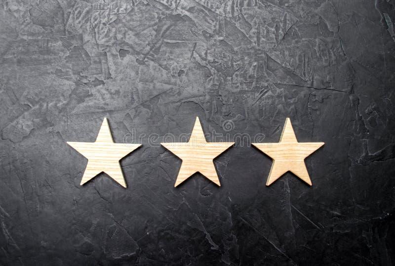 Trzy gwiazdy na ciemnym tle Pojęcie ocena i cenienie Ocena hotel, restauracja, mobilny zastosowanie obraz royalty free