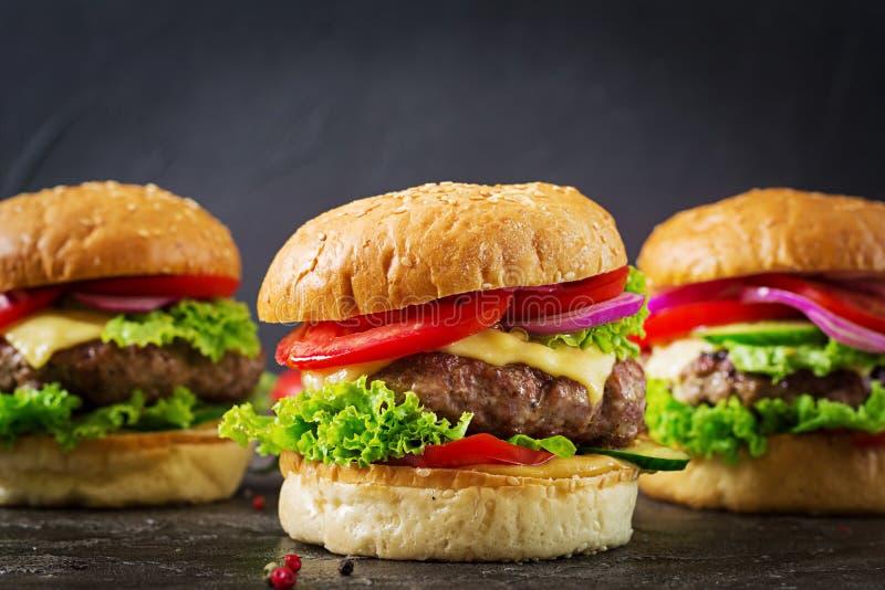 Trzy hamburger z wołowina mięsnym hamburgerem i świeżymi warzywami zdjęcia royalty free