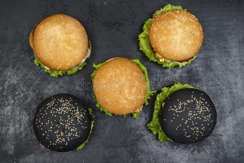 Trzy hamburger z wołowina mięsnym hamburgerem i świeżymi warzywami na ciemnym tle Smakowity jedzenie fotografia stock