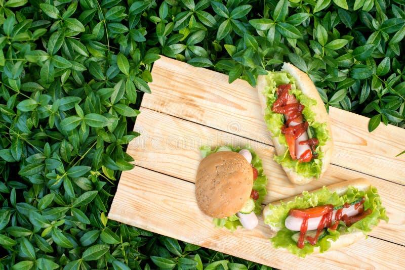 Trzy hamburgeru kłamają na drewnianych deskach na gazonie w ogródzie na a fotografia stock