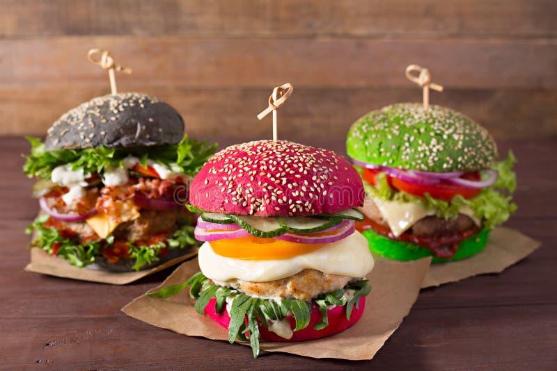 Trzy hamburgeru z różnymi chlebowymi babeczkami czerwienie, zieleń, czarna na drewnianym tle zdjęcia royalty free