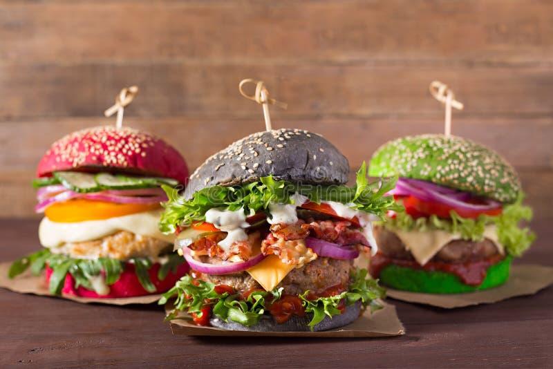 Trzy hamburgeru z różnymi chlebowymi babeczkami na drewnianym tle fotografia royalty free
