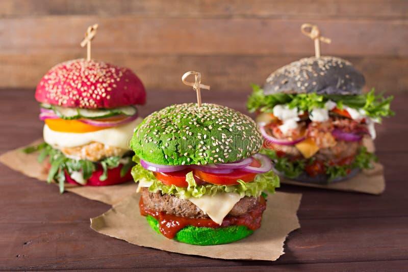 Trzy hamburgeru z różnymi chlebowymi babeczkami na drewnianym tle obrazy stock