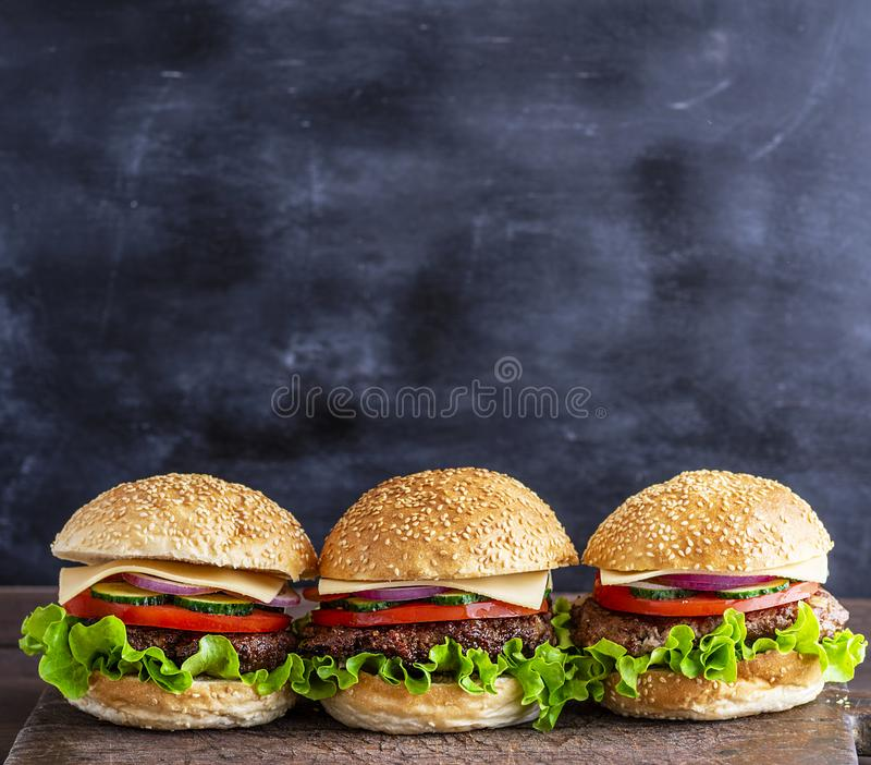 Trzy hamburgeru z warzywami na brown drewnianej desce zdjęcie royalty free