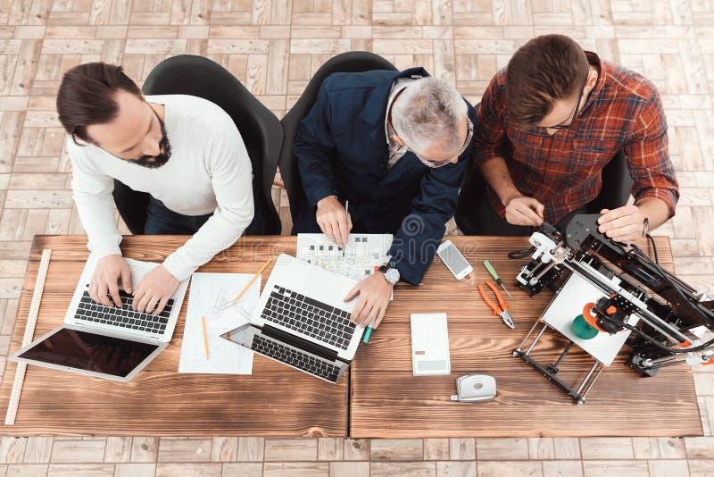 Trzy inżyniera siedzą przy stołem Dwa praca dla komputerów, podczas gdy tercja konfiguruje 3d drukarkę fotografia stock