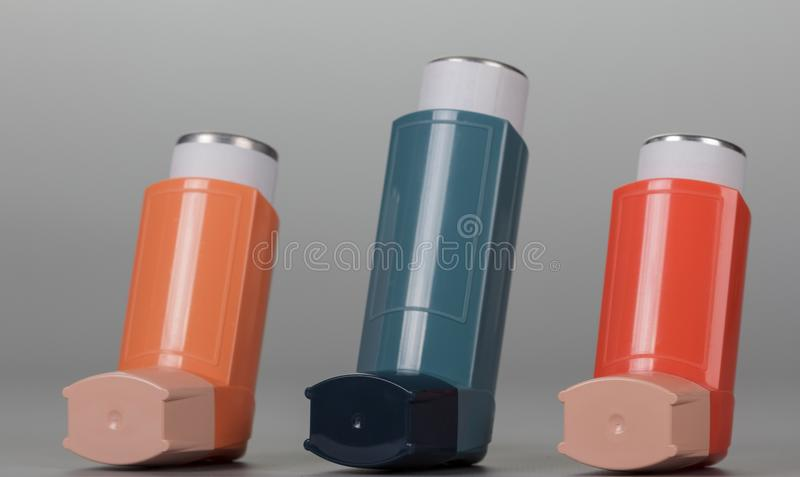 Trzy inhalatorów aerosol na popielatym tle obrazy stock