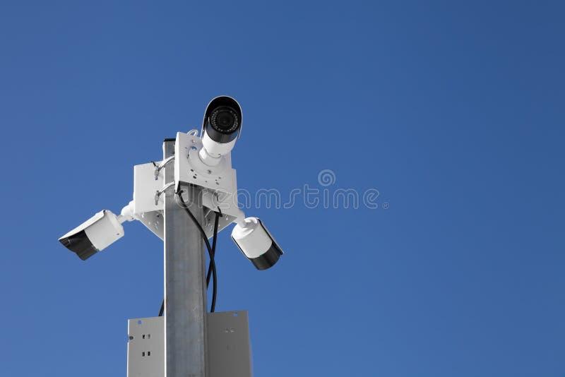 trzy inwigilacji kamery przeciw niebieskiemu niebu obraz stock
