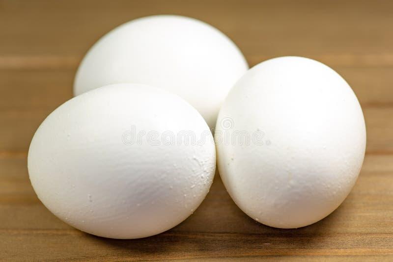 Trzy jajka na kuchennym stole przygotowywającym dla smażyć obrazy royalty free
