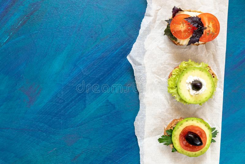 Trzy jarskiej kanapki na pergaminowego papieru kawałku na błękitnym tle z kopii przestrzenią obraz royalty free