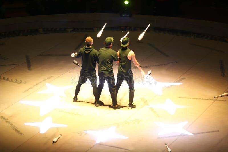 Trzy jugglers/cyrkowi wykonawcy przy pracą na scenie fotografia stock