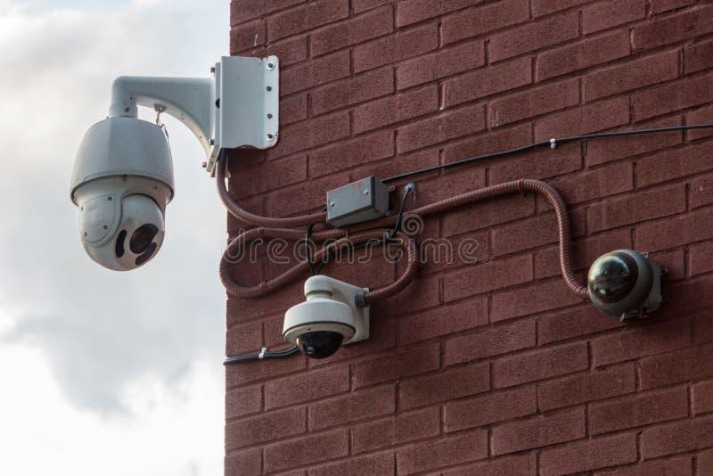 Trzy kamery bezpieczeństwej Wspinającej się na Czerwonej ścianie z cegieł fotografia stock