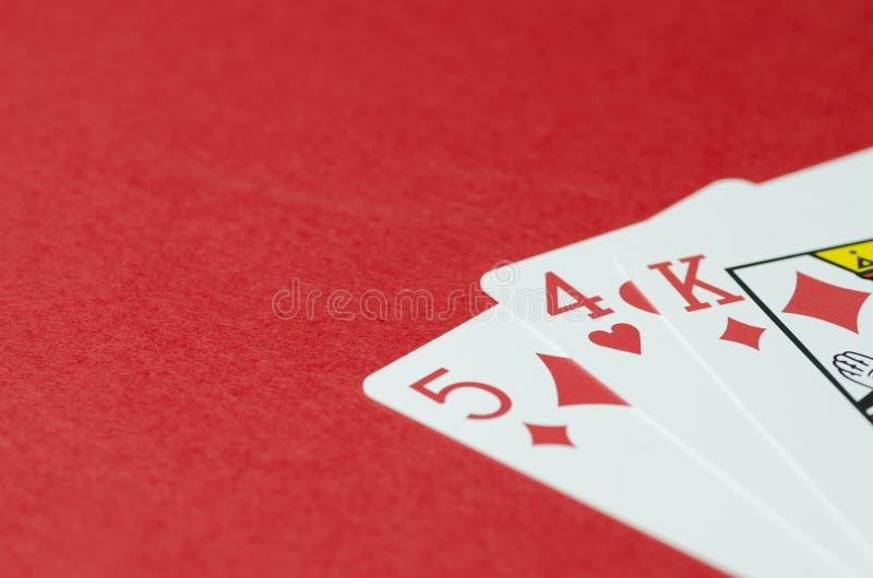 Trzy karty do gry, królewiątko, pięć, cztery na czerwonym tle, opróżniają przestrzeń dla teksta obrazy stock