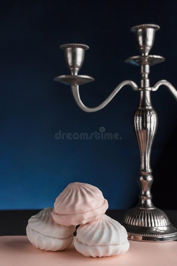 Trzy kawałka zephyr na różowym pastelowym tle blisko candlestick zdjęcie stock