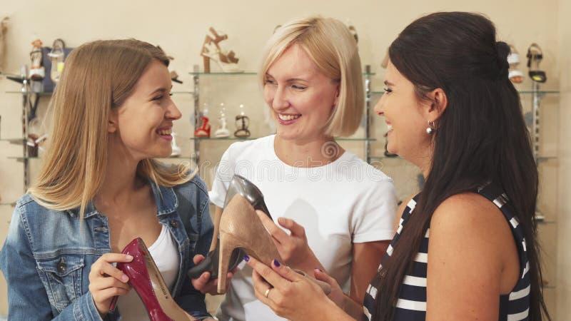 Trzy kobiety dyskutuje buty w obuwianym sklepie obraz stock