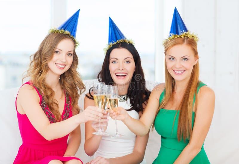 Trzy kobiety jest ubranym kapelusze z szampańskimi szkłami obrazy royalty free