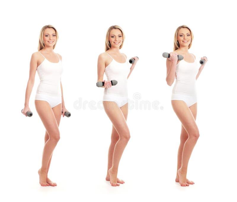 Trzy kobiety w biel odzieżowych mienia dumbbells zdjęcie stock