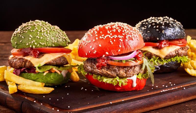 Trzy kolorowego Azjatyckiego hamburgeru z Francuskimi dłoniakami zdjęcie royalty free