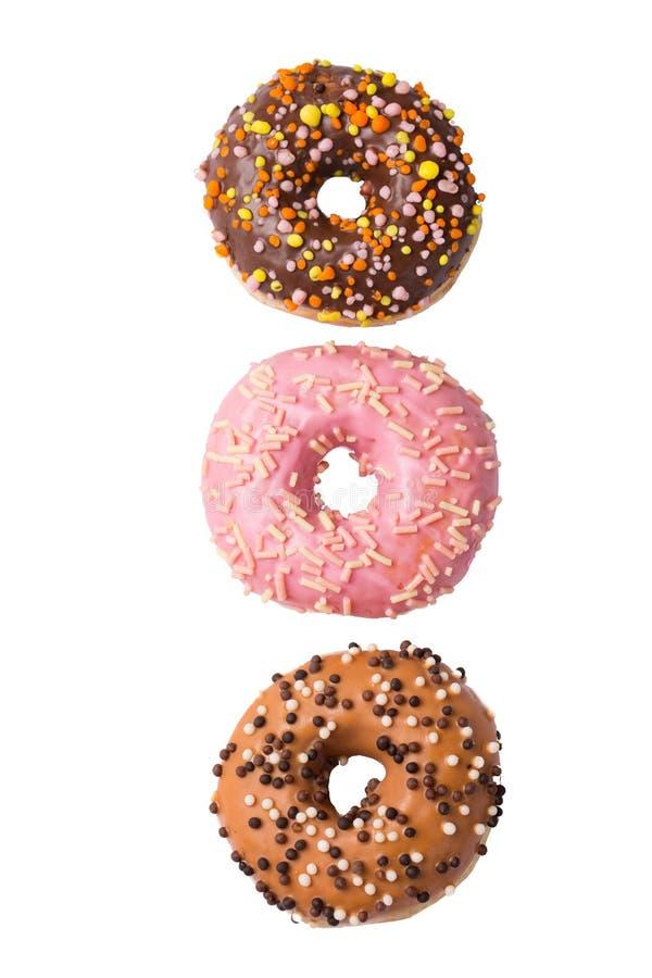 Trzy kolorowego oszklonego donuts odizolowywającego na białym tle, odgórny widok obrazy royalty free