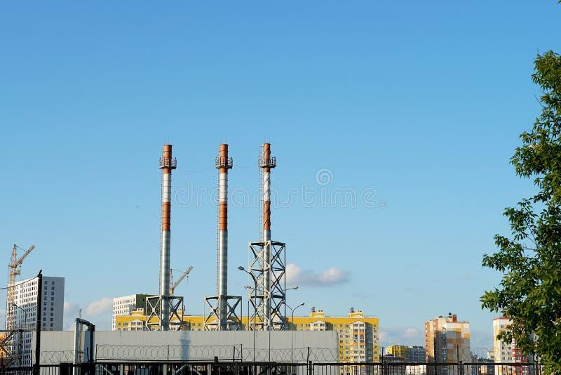 Trzy kominu przeciw niebieskiemu niebu bez dymu, Biel i czerwone drymby ogrzewanie ześrodkowywamy w mieście obrazy stock