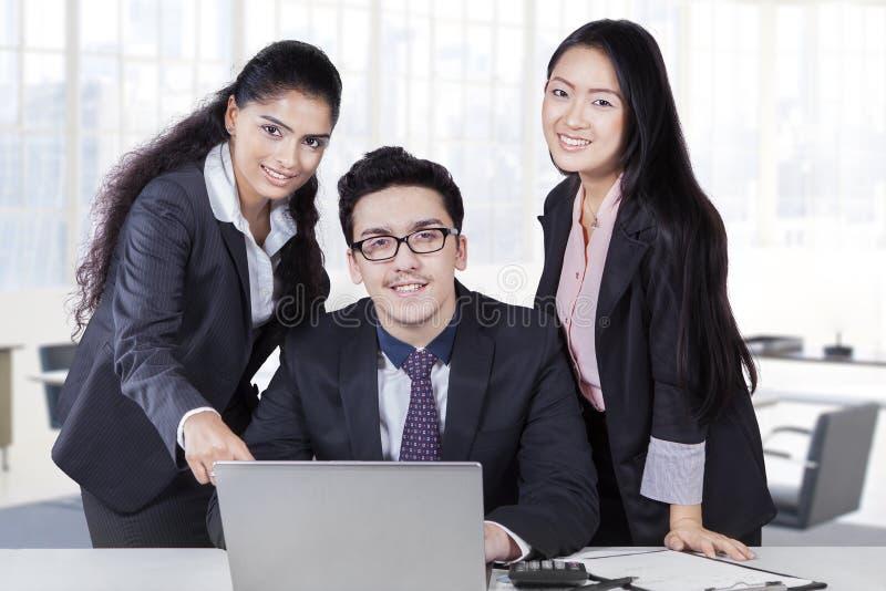 Trzy korporacyjnego pracownika z laptopem w biurze zdjęcie stock