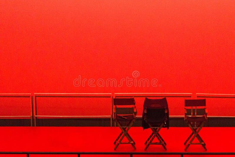 Trzy krzesła na pustej czerwonej scenie zdjęcia royalty free