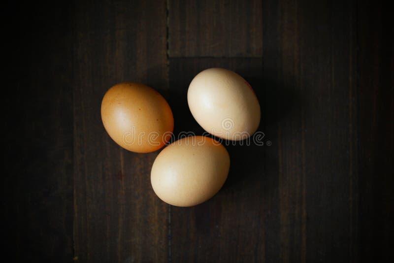 Trzy kurczaka jajka na ciemnym drewnie fotografia stock