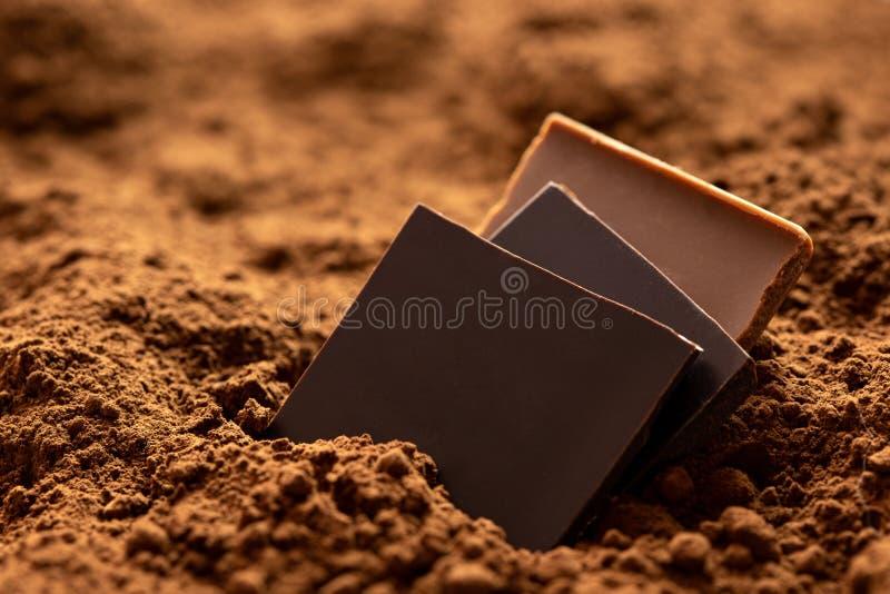 Trzy kwadrata zmrok i dojnej czekolady obsiadanie w kakaowym proszku obrazy stock
