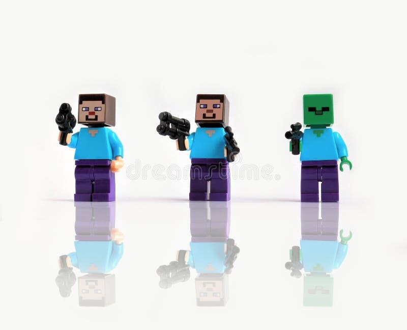 Trzy lego minecraft mini postaci z zabawką strzelają napadanie Odizolowywający na białym tle z odbijającym cieniem obraz stock