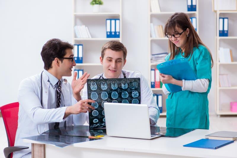 Trzy lekarki dyskutuje obrazów cyfrowych rezultaty promieniowanie rentgenowskie wizerunek obraz stock