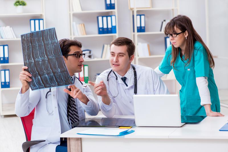 Trzy lekarki dyskutuje obrazów cyfrowych rezultaty promieniowanie rentgenowskie wizerunek zdjęcia stock