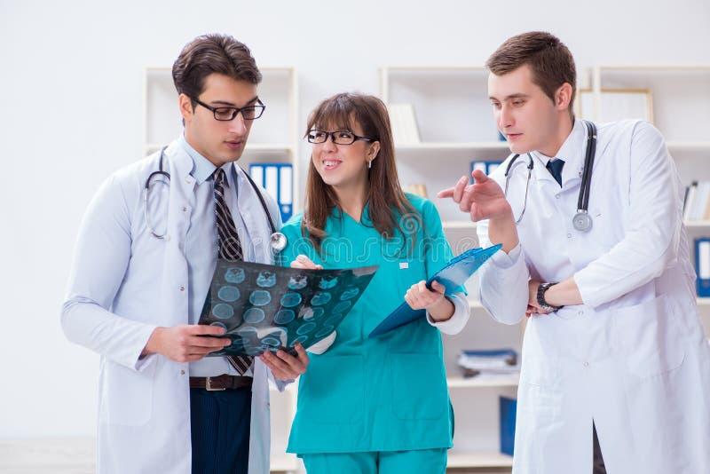 Trzy lekarki dyskutuje obrazów cyfrowych rezultaty promieniowanie rentgenowskie wizerunek zdjęcia royalty free