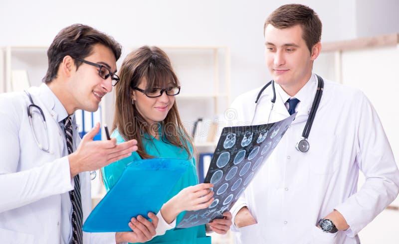Trzy lekarki dyskutuje obraz?w cyfrowych rezultaty promieniowanie rentgenowskie wizerunek zdjęcie royalty free