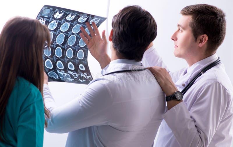 Trzy lekarki dyskutuje obraz?w cyfrowych rezultaty promieniowanie rentgenowskie wizerunek obrazy stock