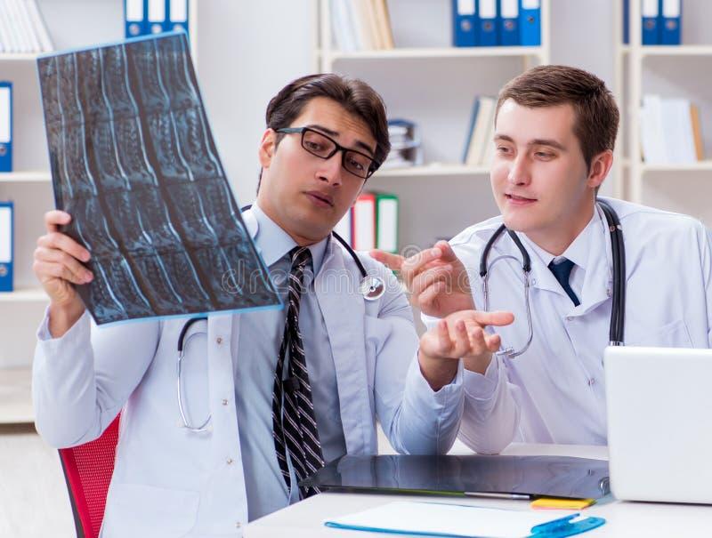 Trzy lekarki dyskutuje obraz?w cyfrowych rezultaty promieniowanie rentgenowskie wizerunek zdjęcia royalty free
