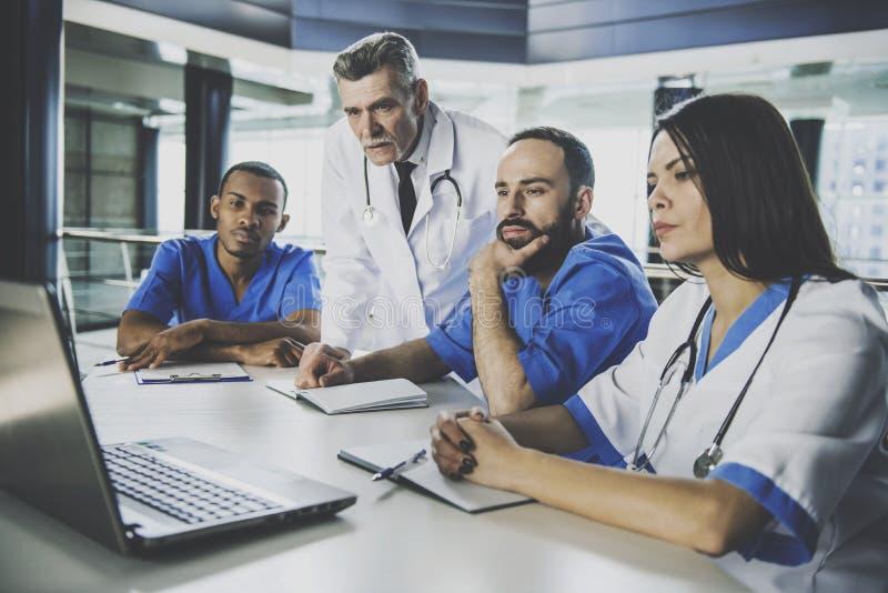 Trzy lekarki Egzamininuje wyniki testu na laptopie obrazy royalty free