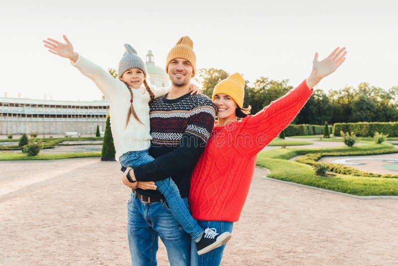 Trzy ludzie dobrego czas wpólnie: matka, ojciec i mały córka stojak obok each inny, spacerów outoors, fala z rękami, h obraz stock