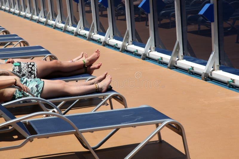 Trzy ludzie sunbathing kłamać na deckchairs zdjęcie stock