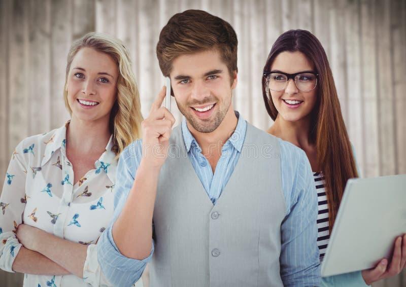 Trzy ludzie z telefonem i laptopem przeciw rozmytemu drewnianemu tłu zdjęcie stock
