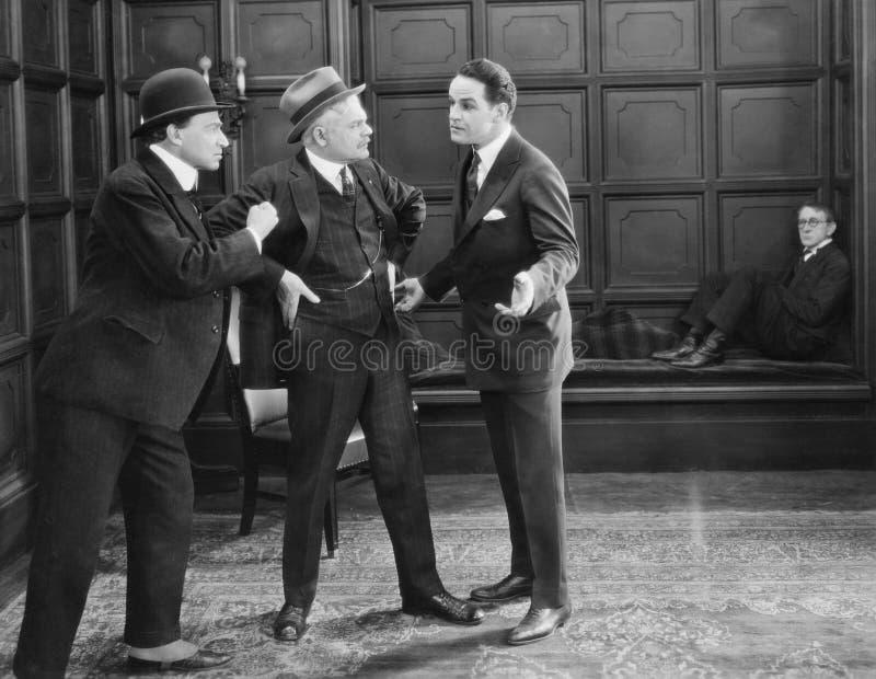 Trzy mężczyzna stoi wpólnie dyskutować (Wszystkie persons przedstawiający no są długiego utrzymania i żadny nieruchomość istnieje zdjęcia stock