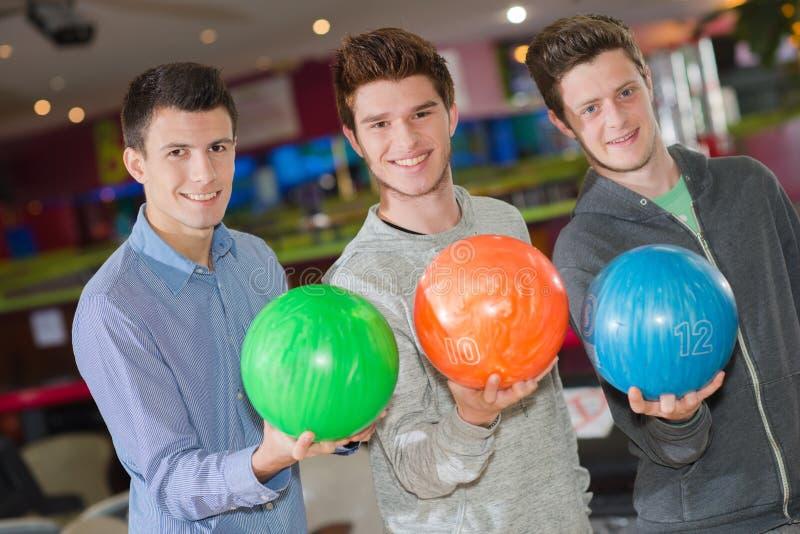 Trzy mężczyzna trzyma kręgle piłki zdjęcie royalty free