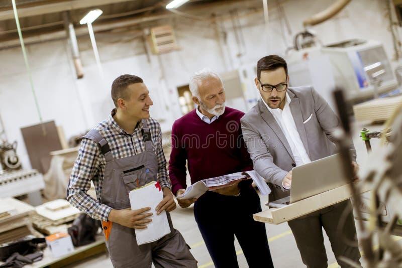 Trzy mężczyzny stoi i dyskutują w meblarskiej fabryce fotografia royalty free