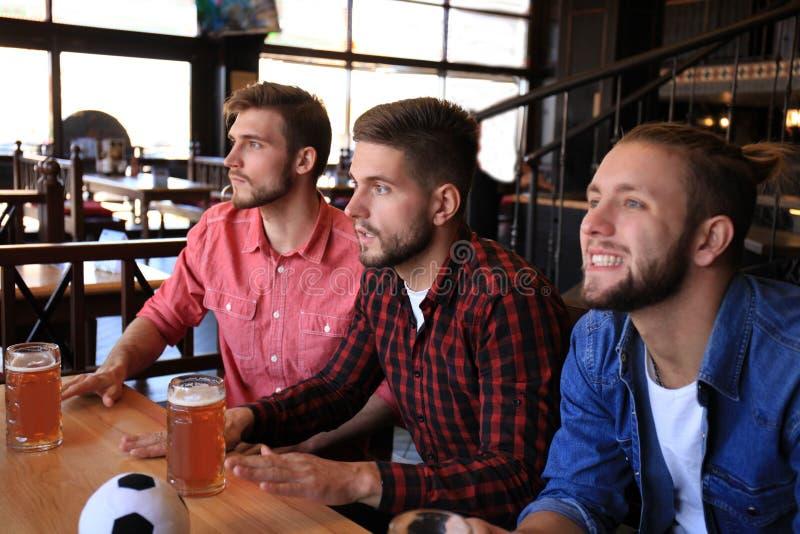 Trzy m??czyzny w przypadkowych ubraniach rozweselaj? dla futbolu i trzymaj? butelki piwo podczas gdy siedz?cy przy barem odpieraj obraz royalty free