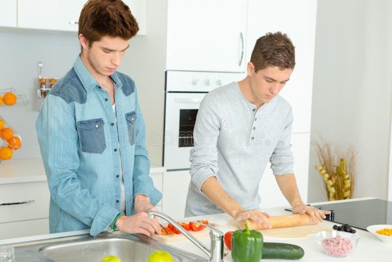 Trzy Męskiego przyjaciela Robi pizzy W kuchni Wpólnie obrazy stock