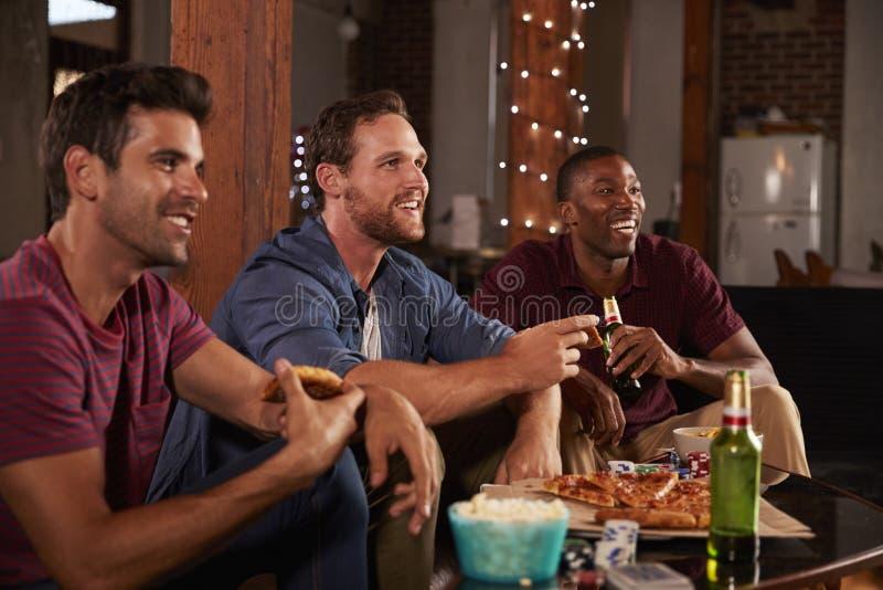 Trzy męskiego przyjaciela wieszają oglądać TV jeść pizzę i fotografia stock