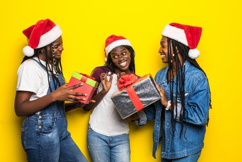 Trzy młode kobiety afrykańskie w kostiumie Świętego Mikołaja z teraźniejszością na żółtym tle obrazy royalty free