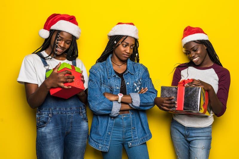 Trzy młode kobiety afrykańskie w kostiumie Świętego Mikołaja z teraźniejszością na żółtym tle fotografia royalty free